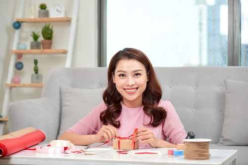 Step by step, smiling asian woman wrapping gifts for the holiday