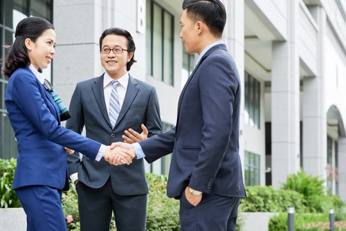 Adult Asian man and woman shaking hands with smiling colleague