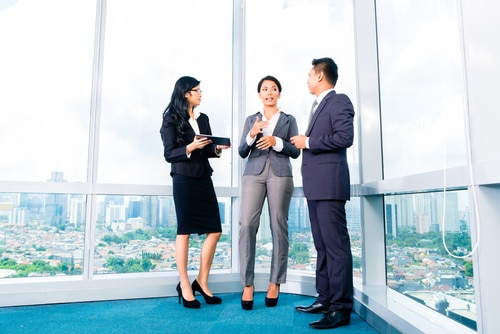 Asian Businesspeople standing and talking to each other