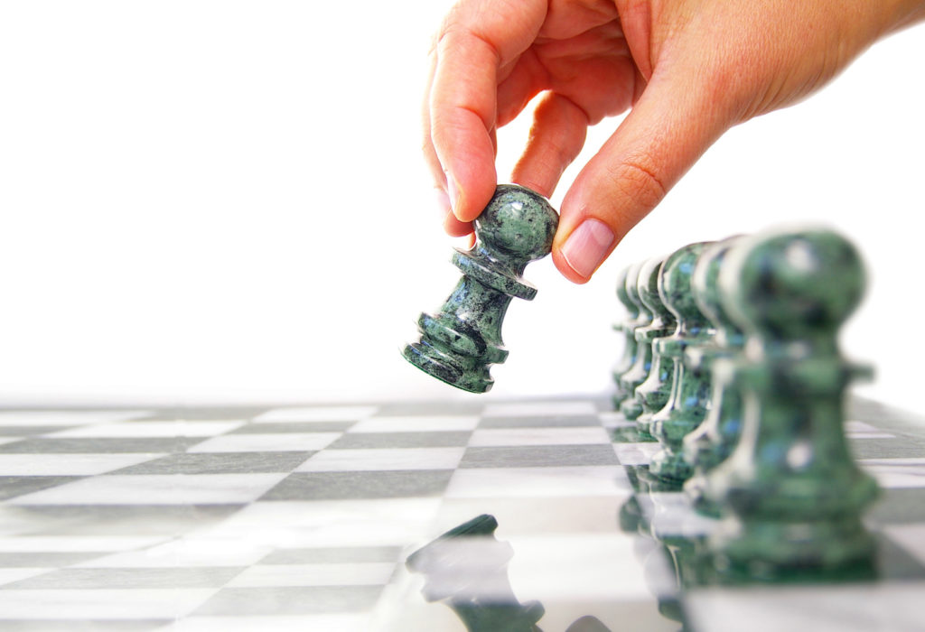 Woman moving a chess piece forward, isolated on white
