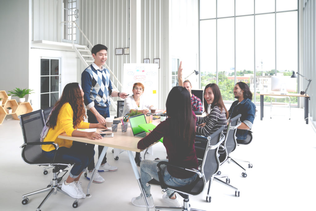 Group of multiracial young creative team talking, laughing and brainstorming in meeting at modern office concept. Man standing and female raising hand for sharing while sitting together in rear view
