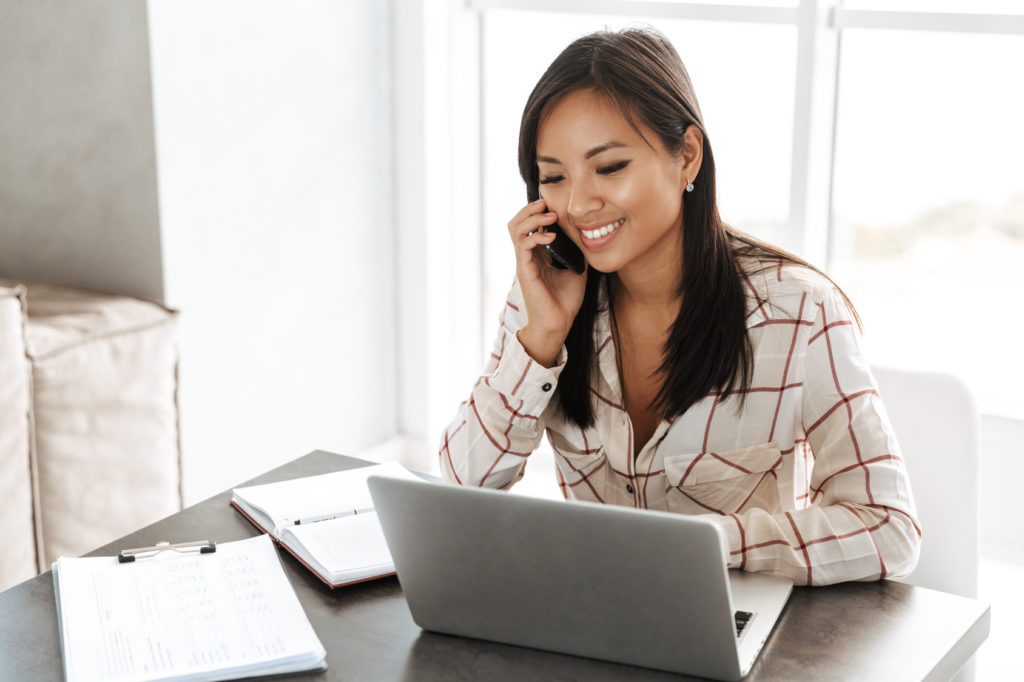 Image of joyous asian woman 20s talking on smartphone and working on laptop while sitting at table indoor