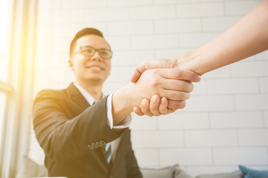 Asian businessman shaking hand with partnership and smile