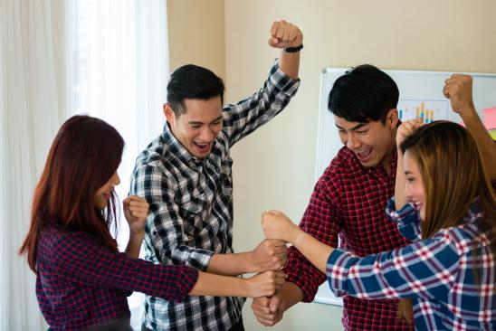 employees piling their hands to create a tower (teamwork)