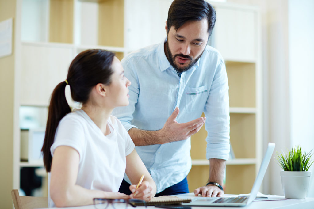 Portrait of adult Asian man leaning to help young woman at desk in office and discuss work