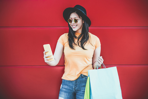 Happy trendy asian girl using shopping app holding bags outdoor